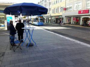 """Der Infostand mit Bistrotisch und Schirm in der Fußgängerzone """"Obere Königstraße"""" am 29.09.2018 in Kassel."""