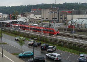 Der Bahnhof in Wetzlar, hier gibt es im Bahnhofsgebäude direkt an der Südseite der Gleise und in unmittelbarer Nachbarschaft zum zentralen Busknoten wieder einen Fahrkartenkartenschalter. Im Vordergrund ein Zug der Linie RB 40 (Mittelhessen-Express) mit einem Talent 2 von DB Regio.